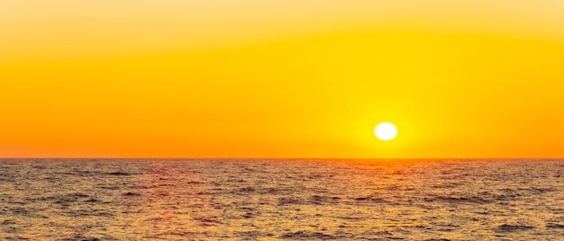 海に沈むオレンジ色の夕日。海の地平線上の明るい太陽。コンセプト休暇、リラックス、ロマンチック
