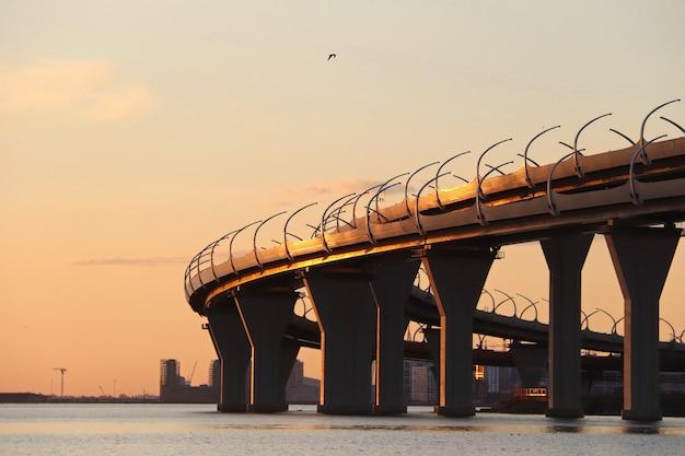 Оранжевый закат над рекой с автомобильного моста