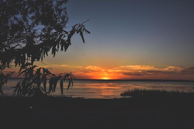 川に沈むオレンジ色の夕日