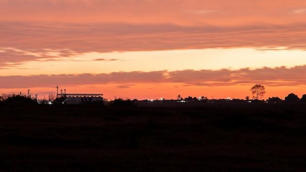 극적인 구름과 브라질 도시 카실란디아의 실루엣이 있는 주황색 일몰