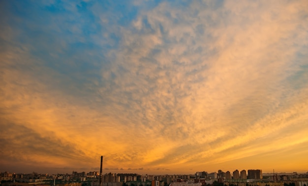 Orange sunset with textured clouds over the city.