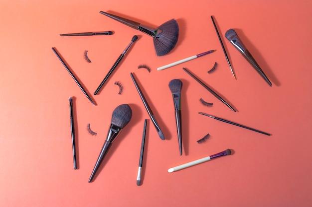 プロフェッショナルな使用のためのさまざまな化粧ブラシとつけまつげがあるオレンジ色の表面