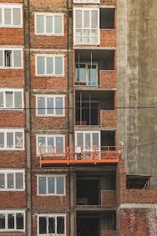 오렌지 매달린 건설 크래들은 주택 건설의 높은 층에서 들어 올려 작업을 위해 건설중인 집의 외관에 달려 있습니다.