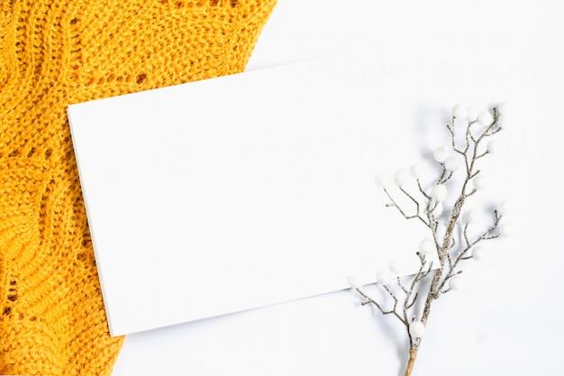 Оранжевый свитер, лист белой бумаги и декоративная веточка на белом фоне