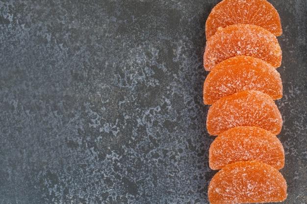 Marmellata di gelatina dolce all'arancia su fondo di marmo. foto di alta qualità