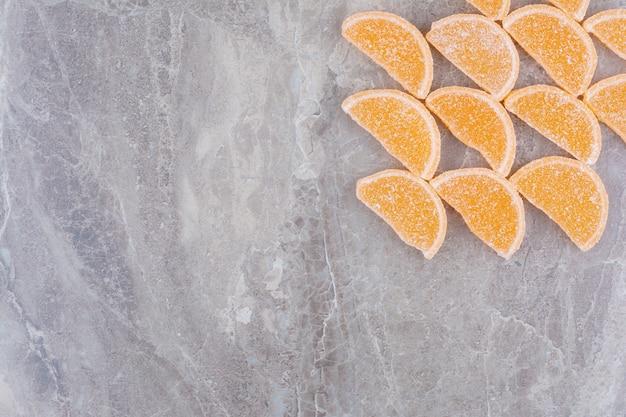 大理石の背景にオレンジ色の甘いマーマレード