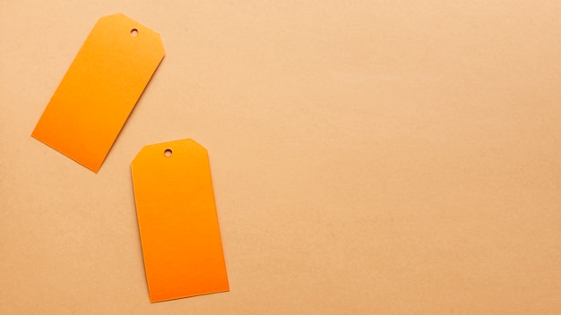 Orange tags on neutral carboard sheet with copy space