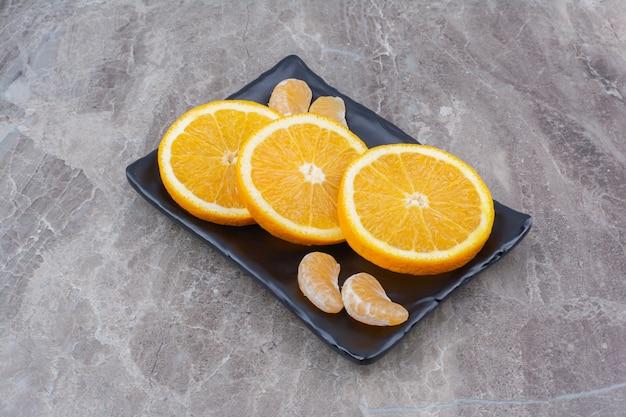 Orange and tangerine slices on black plate.