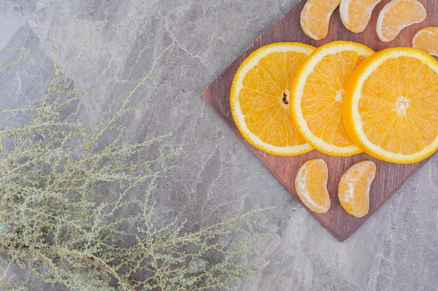 Orange and tangerine slices on wooden board.