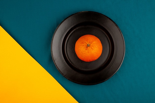 Orange tangerine a top view of fresh ripe mellow juicy whole inside black plate on a yellow-blue floor