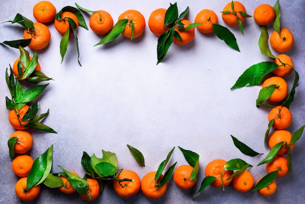 Orange tangerines (oranges, mandarins, clementines, citrus fruits) with green leaves on light background, copy space
