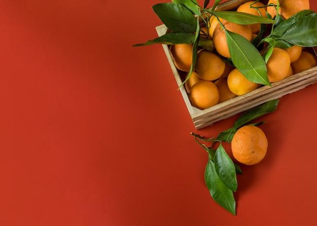 赤の木製バスケットに緑の葉を持つオレンジのみかん