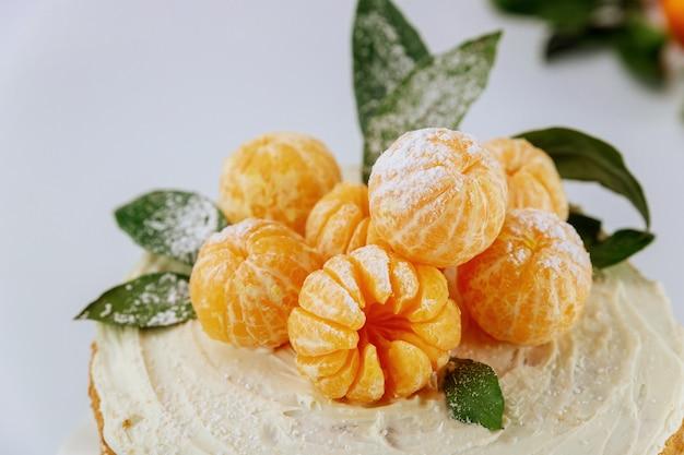 緑の葉を持つオレンジのみかんがクローズアップ。