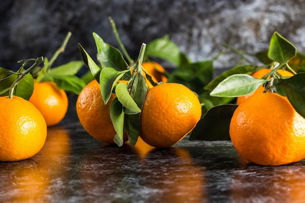 Orange tangerines with green leaves on dark background