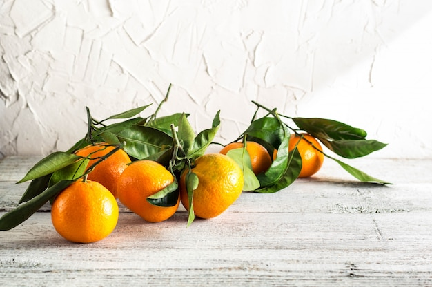 Orange tangerines with green leaves on white wooden background