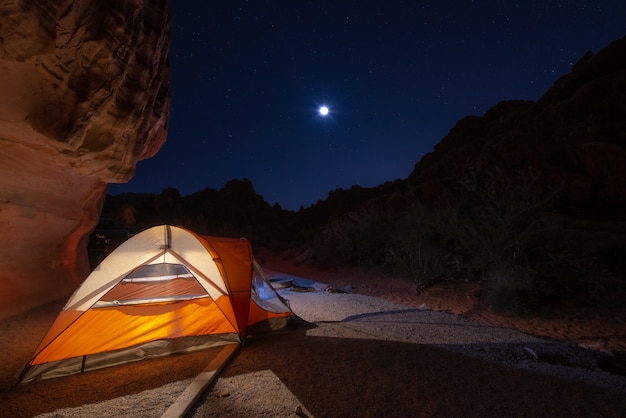 Orange tent camping at night with fuul moon and full of stars in the sky