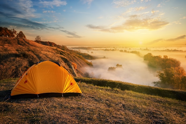 Orange tent in canyon over misty river at sunset