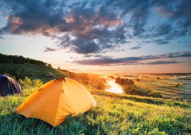 Оранжевая палатка на холме над рекой
