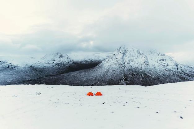 Оранжевые палатки у заснеженной горы
