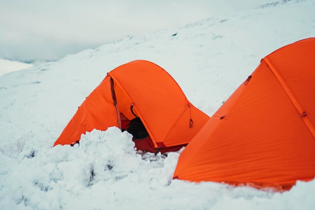 Orange tents at a snowy mountain