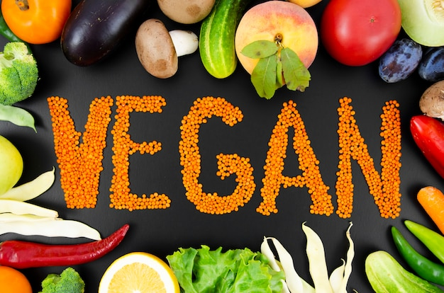 Orange text vegan surrounded by fresh fruits and vegetables