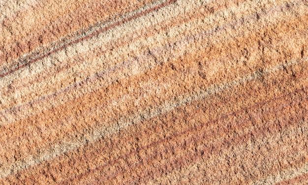 天然天然石の赤い縞とオレンジ色のテクスチャ。砂岩。デザインの背景。