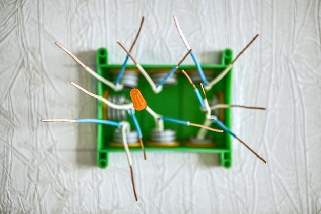 가정용 배선의 전기 정션 박스에 구리선을 연결하기 위한 주황색 나사산 캡 또는 나사식 와이어 커넥터. 얕은 피사계 심도로 촬영하고 배경을 흐리게 합니다.