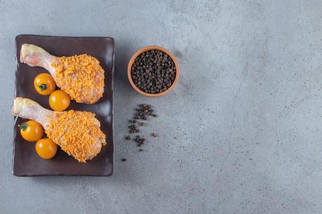Оранжевые помидоры и куриные голени на блюде рядом с миской для специй на мраморном фоне.