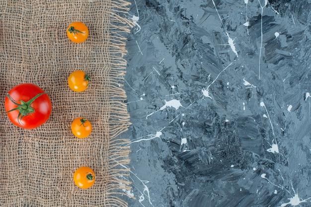 大理石の背景に、黄麻布のナプキンにオレンジ色のトマトと赤いトマト。