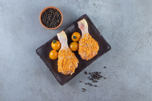 Orange tomatoes and chicken drumsticks on a platter next to spice bowl , on the marble background.