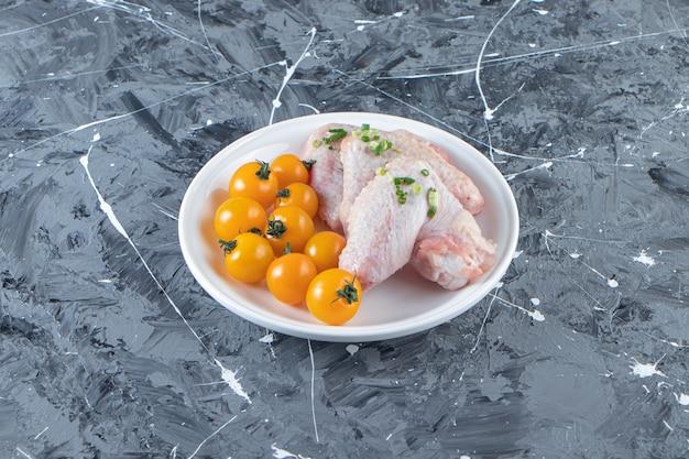 Pomodori arancioni e ali di pollo su un piatto, sulla superficie di marmo.