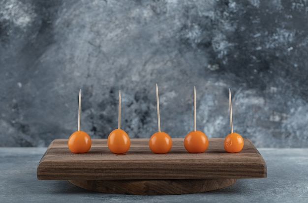 Orange tomatoes with sticks on wooden board.