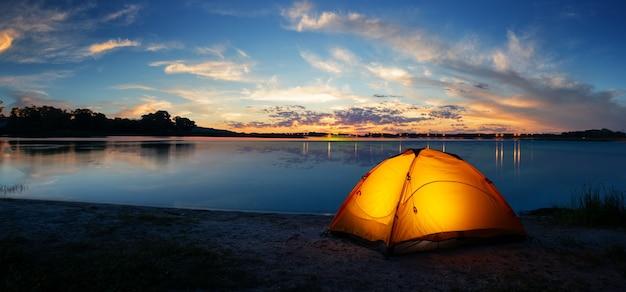 Оранжевая туристическая освещенная палатка у озера на закате