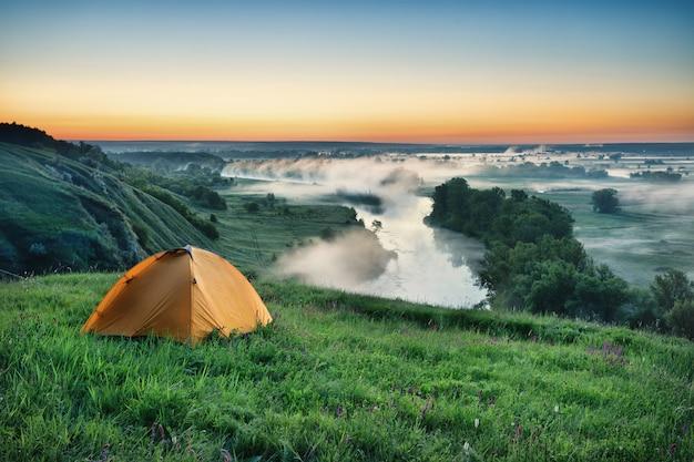 Оранжевая туристическая палатка на склоне холма