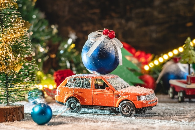 Orange toy car is going along a snow covered road and carrying a blue christmas ball