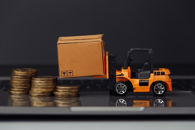 Orange toy forklift with carton boxes and coins on keyboard close-up. logistics and delivery concept