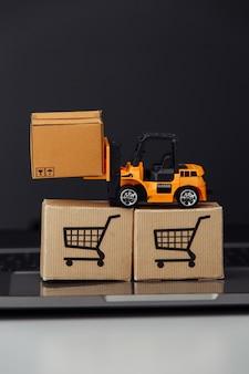 キーボードのカートンボックスとオレンジ色のおもちゃのフォークリフト。ロジスティクスと配送のコンセプト。垂直方向の画像