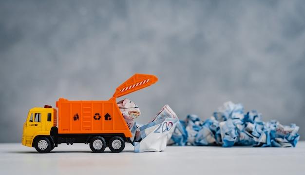 Оранжевый игрушечный мусоровоз выгружает скомканные бумажные банкноты на белом столе на синем фоне.