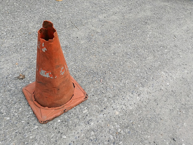 Orange traffic cone on asphalt road with white arrow to turn left ahead.