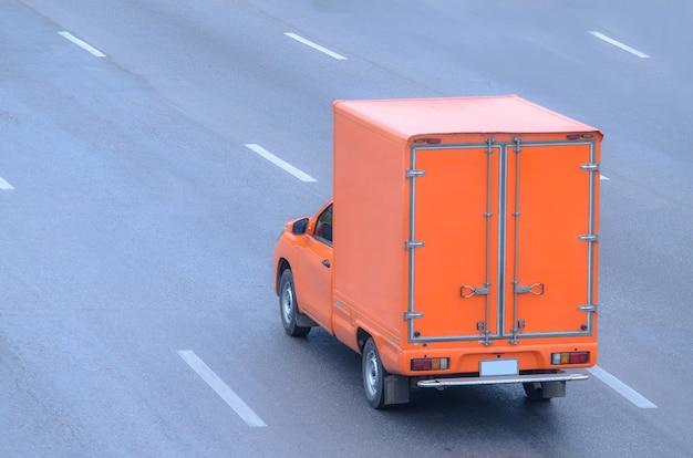 도로 위를 달리는 주황색 트럭, 도로 위의 작은 트럭.