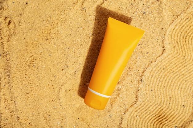 Orange tube of sunscreen on beach sand. sun protection. top view