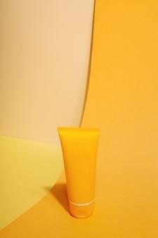 Orange tube of sunscreen on orange background sun protection