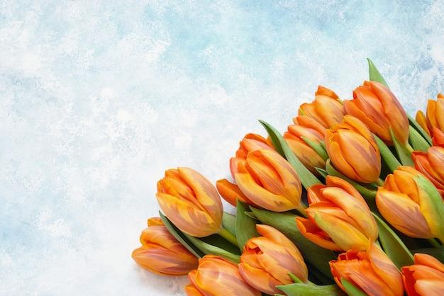 Букет оранжевых тюльпанов на синем акварельном фоне, копия пространства, вид сверху, праздничный фон