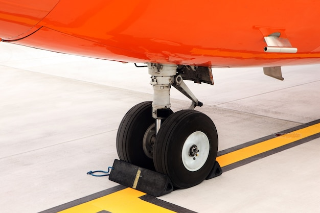An orange undercarriage of a business jet standing on the apron