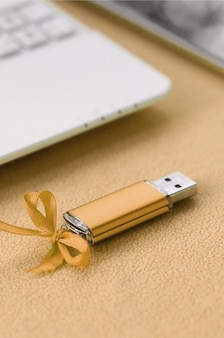 Orange usb flash memory card with a blue bow lies on a blanket of soft and furry light orange fleece fabric beside to a white laptop and smartphone.