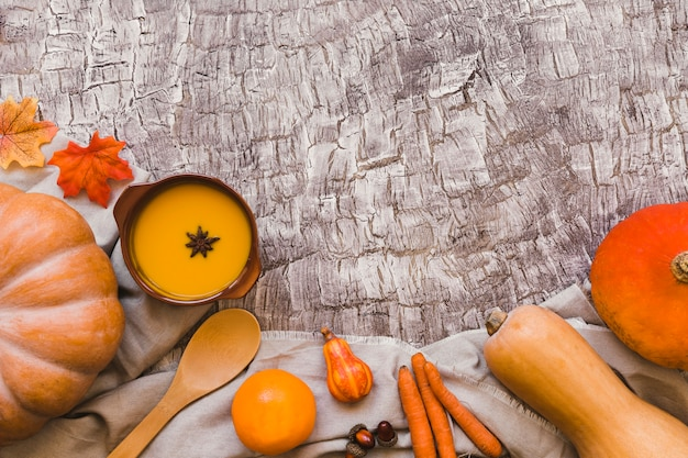 Orange vegetables and fruits near soup