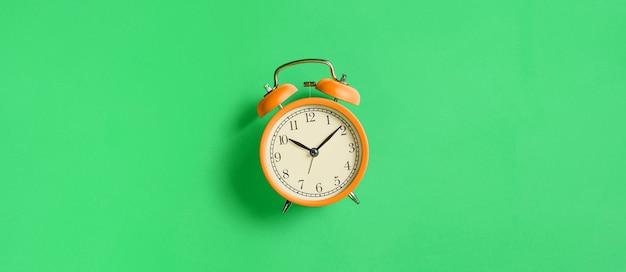 緑の背景にオレンジ色のヴィンテージ目覚まし時計。上面図。フラットレイ、コピースペース