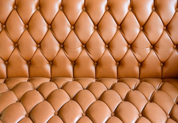 Orange vintage leather sofa buttoned of textured background Premium Photo