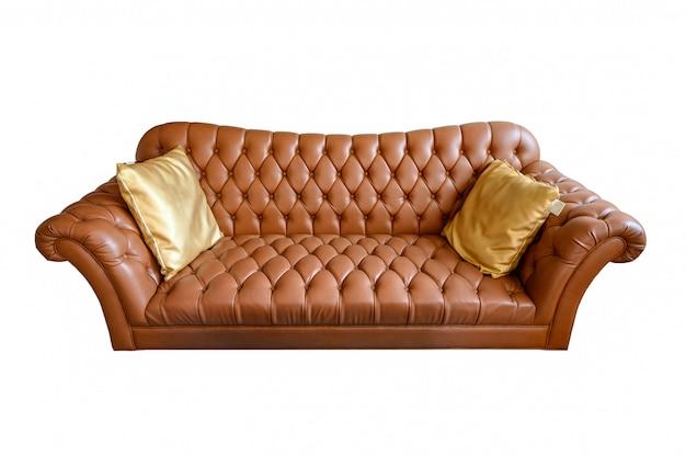金色の枕でボタンをかけたオレンジ色のビンテージレザーのソファ。背景に分離