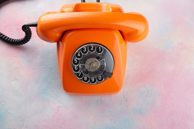 Orange vintage telephone on a multi-colored table - top view